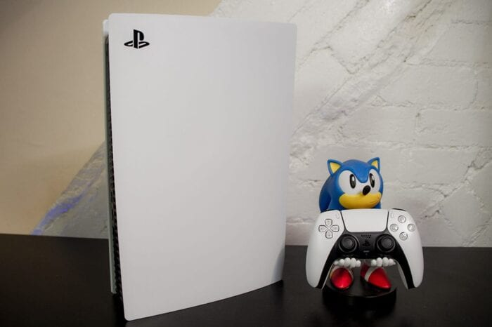 A photo of the PlayStation 5 with a Sonic the Hedgehog figure holding the DualSense controller.